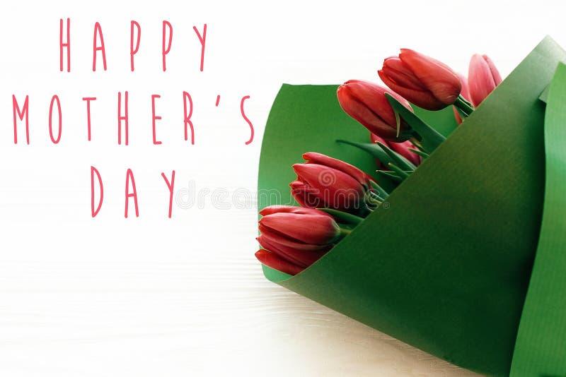 El texto feliz del día de madre y los tulipanes rojos hermosos en el fondo de madera blanco plano ponen Tarjeta de felicitación f fotos de archivo