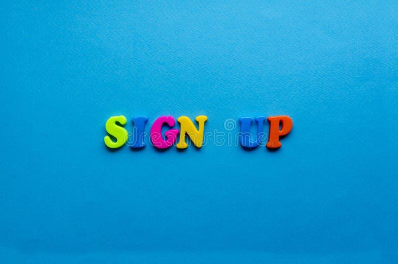 El texto firma para arriba de letras coloreadas plásticas en fondo de papel azul imagen de archivo libre de regalías