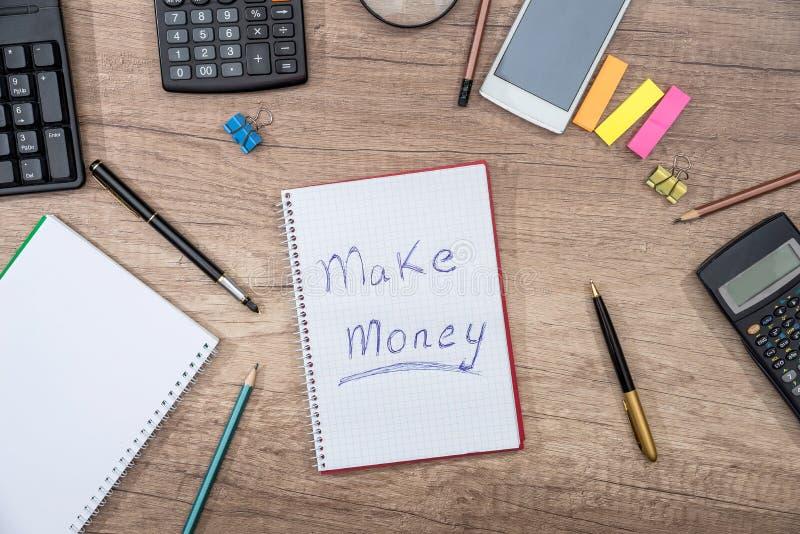 el texto hace el dinero en la libreta con el teclado del smartphone, pluma, calculadora fotografía de archivo libre de regalías