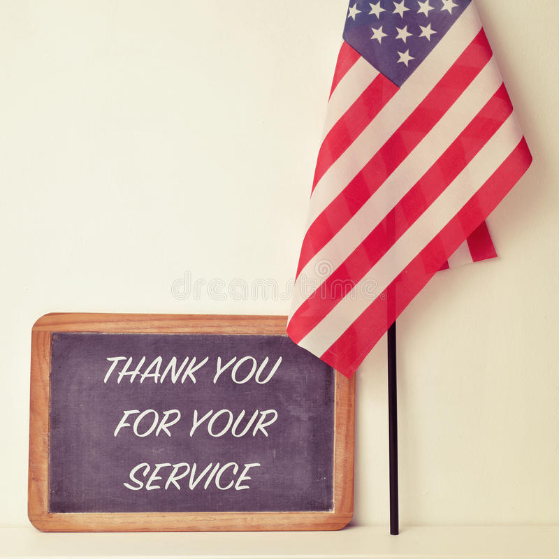 El texto le agradece por su servicio en una pizarra y la bandera de foto de archivo libre de regalías