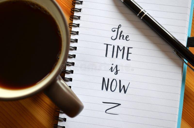 El ` el tiempo ahora es ` mano-indicado con letras en cuaderno fotos de archivo libres de regalías