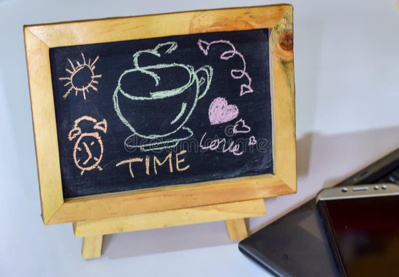 El tiempo de la frase es amor escrito en una pizarra en él y el smartphone, ordenador portátil fotos de archivo libres de regalías