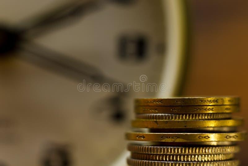 El tiempo es oro Primer de monedas apiladas y de un despertador imagen de archivo libre de regalías