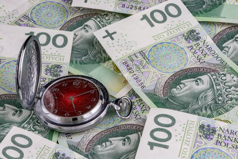 El tiempo es oro, pula 100 billetes de banco del zloty con el reloj tradicional fotografía de archivo libre de regalías