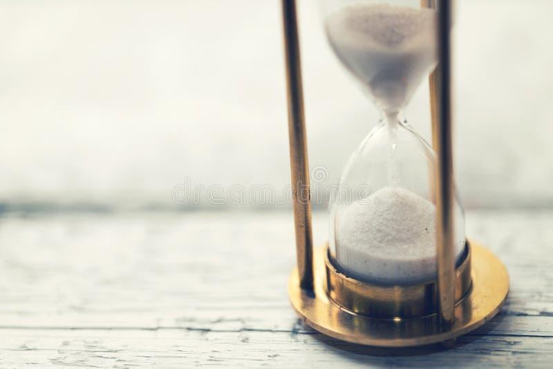 El tiempo está haciendo tictac - reloj de arena en la tabla con el espacio de la copia imagenes de archivo