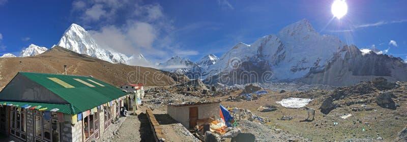 El tiempo hermoso en Gorak Shep con las pensiones nepalesas y nieve capsuló la gama Himalayan en el fondo fotografía de archivo libre de regalías