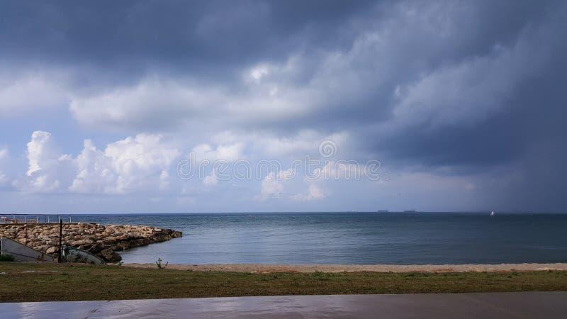 El tiempo nublado en la costa, personas que practica surf monta en la lluvia, colgando se nubla imágenes de archivo libres de regalías