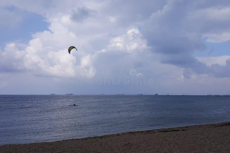 El tiempo nublado en la costa, personas que practica surf monta en la lluvia, colgando se nubla foto de archivo libre de regalías