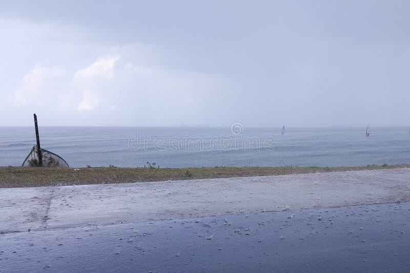 El tiempo nublado en la costa, personas que practica surf monta en la lluvia, colgando se nubla imagen de archivo