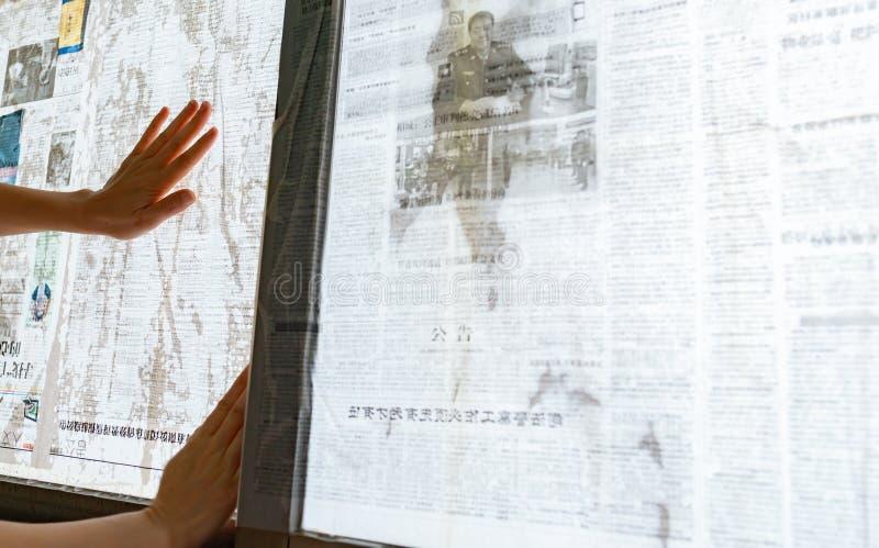 El tifón estupendo Mangkhut va a China y a una señora que pega el periódico a las ventanas de cristal para reforzarlas foto de archivo libre de regalías