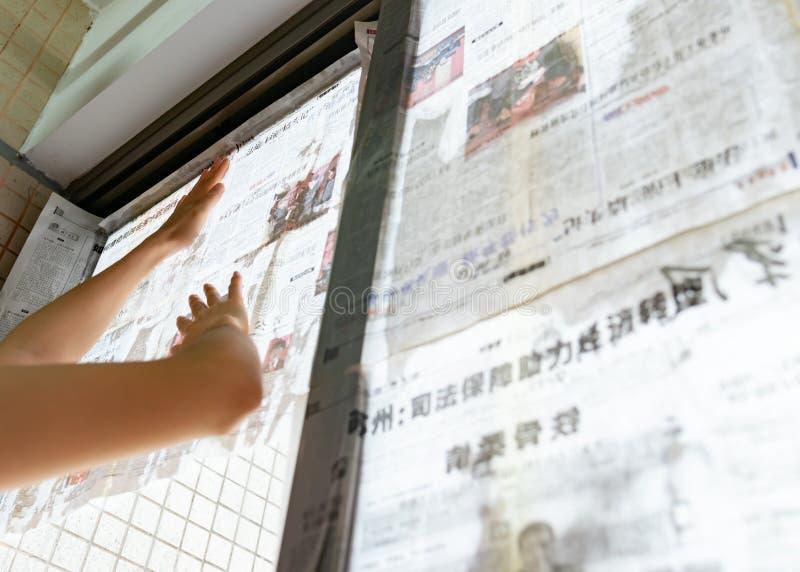 El tifón estupendo Mangkhut va a China y a una señora que pega el periódico a las ventanas de cristal para reforzarlas fotografía de archivo libre de regalías