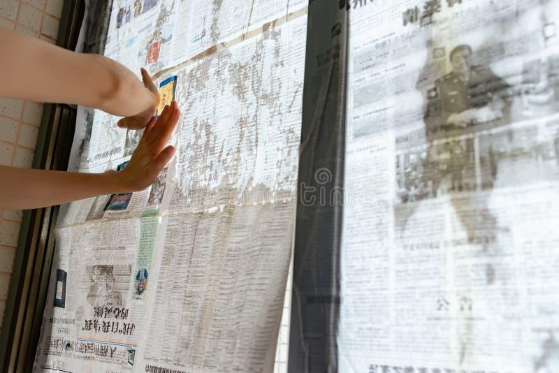 El tifón estupendo Mangkhut va a China y a una señora que pega el periódico a las ventanas de cristal para reforzarlas fotos de archivo libres de regalías