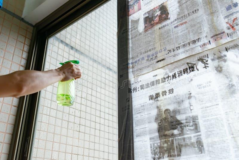 El tifón estupendo Mangkhut va a China y a una señora que pega el periódico a las ventanas de cristal para reforzarlas imágenes de archivo libres de regalías