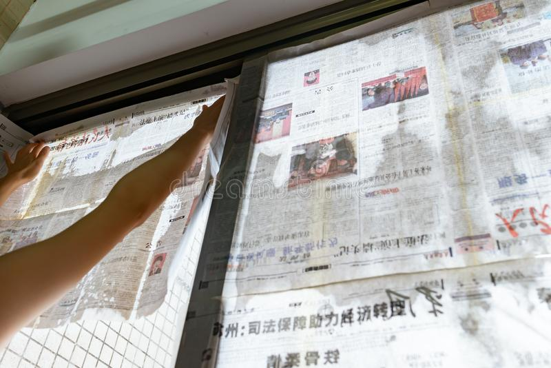 El tifón estupendo Mangkhut va a China y a una señora que pega el periódico a las ventanas de cristal para reforzarlas foto de archivo
