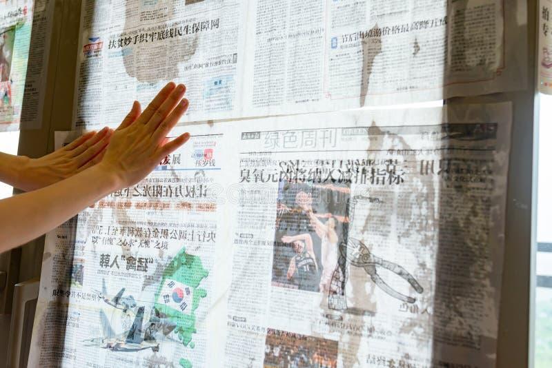 El tifón estupendo Mangkhut va a China y a una señora que pega el periódico a las ventanas de cristal para reforzarlas imagen de archivo