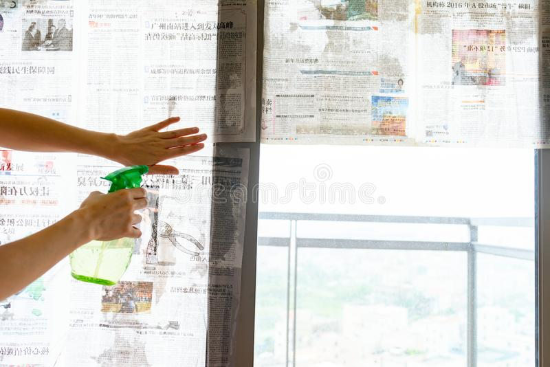 : El tifón estupendo Mangkhut va a China y a una señora que pega el periódico a las ventanas de cristal para reforzarlas imagen de archivo libre de regalías