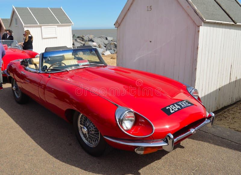 El tipo clásico coche de tragante abierto del rojo E de deportes de Jaguar parqueó en la 'promenade' de la orilla del mar cerca d imagenes de archivo