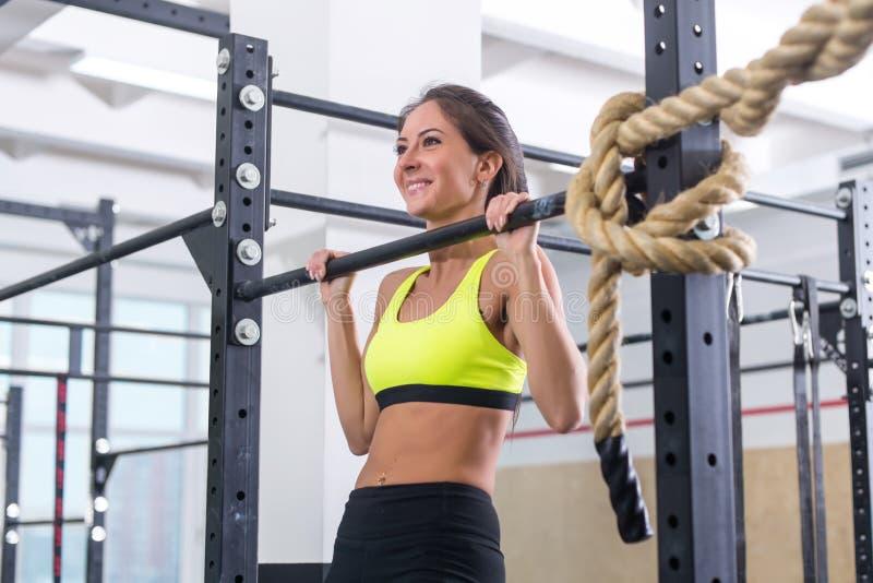 El tirón de la mujer de la aptitud sube en barra horizontal en gimnasio imagenes de archivo