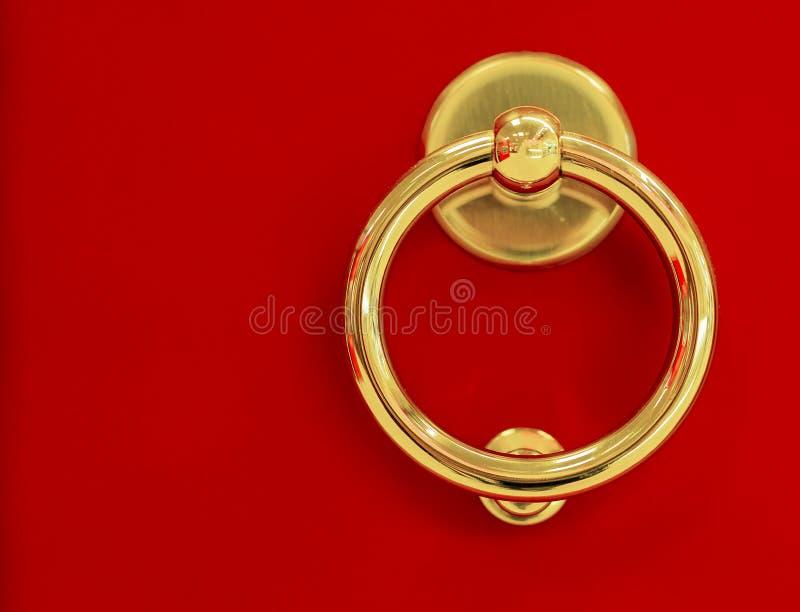 El tirador de puerta redondo en un fondo rojo foto de archivo libre de regalías