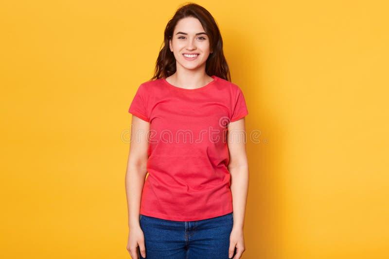 El tiro aislado de la muchacha morena bastante adulta con sonrisa amplia, lleva el equipo casual, siendo entretenido por los amig imagen de archivo libre de regalías