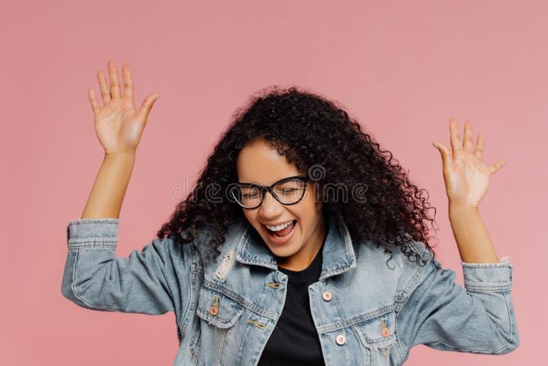 El tiro aislado de la mujer feliz hermosa con el peinado rizado, mantiene las manos aumentadas, las risas de emociones positivas, imagen de archivo libre de regalías