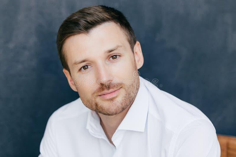 El tiro aislado del trabajador corporativo de sexo masculino joven hermoso se vistió en la camisa blanca elegante, actitudes cont foto de archivo libre de regalías
