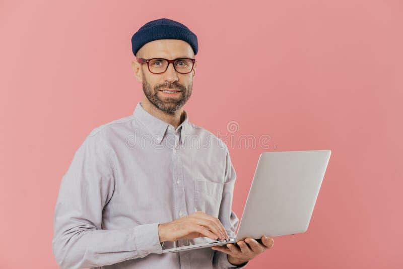 El tiro aislado del varón sin afeitar hermoso hace trabajo de la distancia en el ordenador portátil portátil, lleva el sombrero y foto de archivo libre de regalías