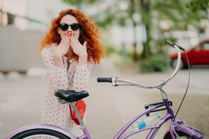 El tiro al aire libre de cubiertas femeninas pelirrojas magn?ficas articula con ambas palmas, tiene manicura roja, vestida en ves foto de archivo libre de regalías