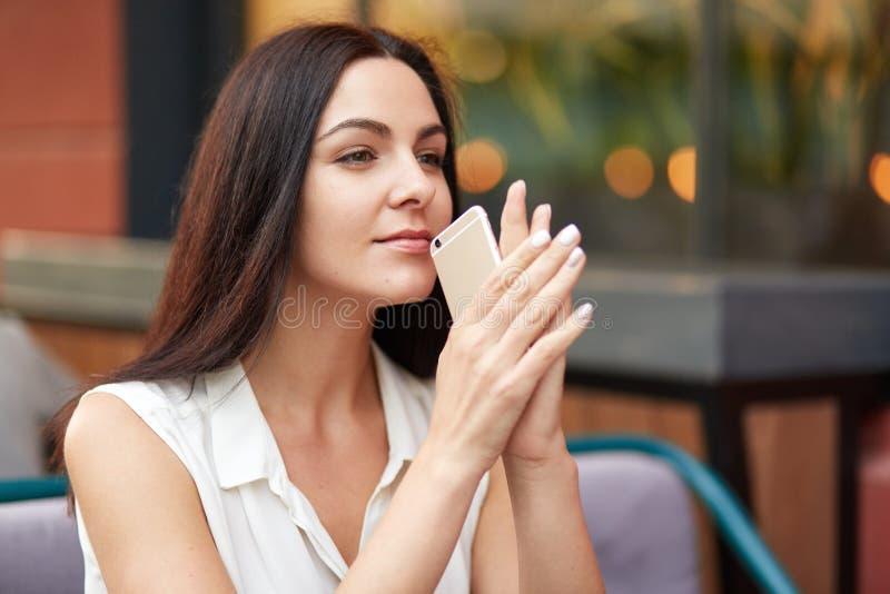 El tiro al aire libre de la hembra morena con la expresión seria, controles teléfono elegante, esperas para la llamada importante foto de archivo libre de regalías