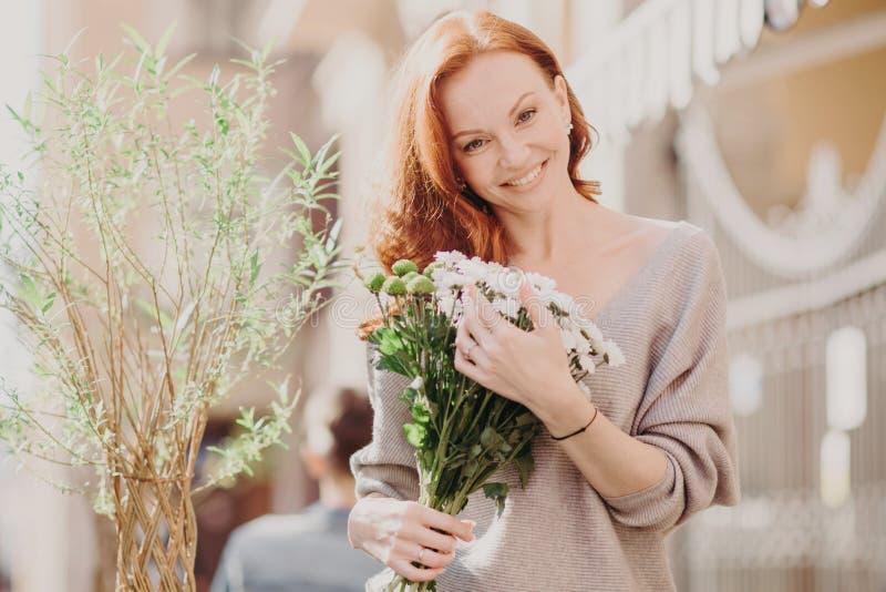 El tiro al aire libre de la mujer astuta preciosa inclina a la cabeza, feliz de recibir las flores del novio, vestido en ropa cas fotografía de archivo