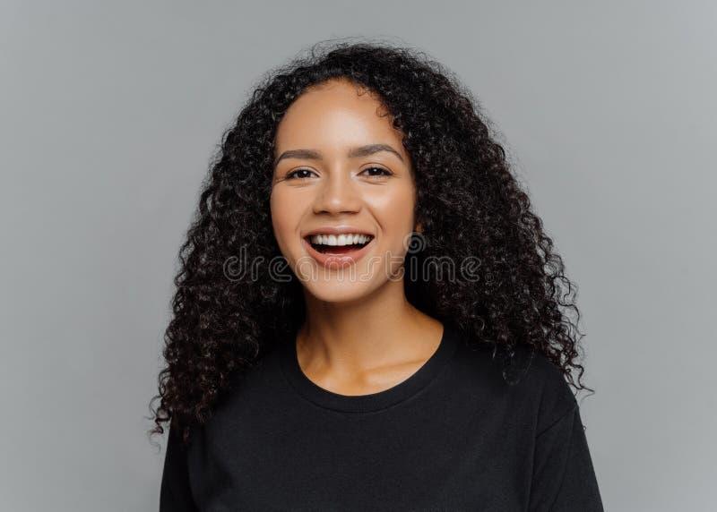El tiro ascendente cercano de la mujer afroamericana pelada oscura feliz ríe positivamente, estando en el buen humor, vestido en  imagen de archivo libre de regalías