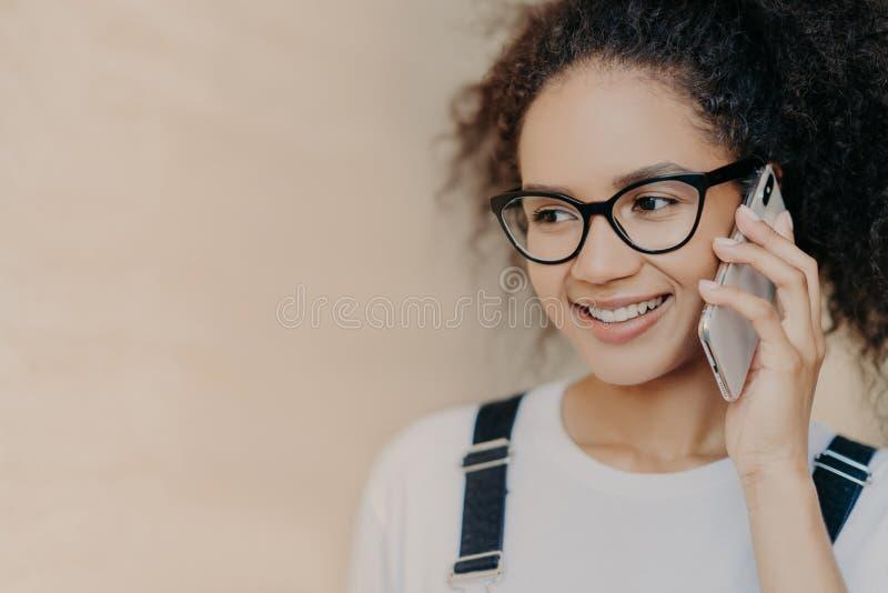 El tiro ascendente cercano de la mujer pelada oscura feliz con negociaciones del peinado del Afro vía el teléfono móvil, sonríe s foto de archivo