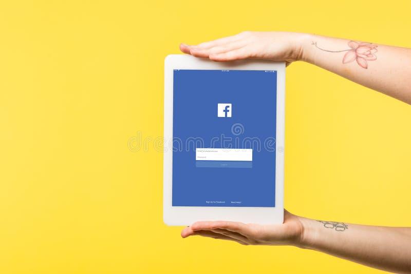el tiro cosechado de la persona que sostenía la tableta digital con el app del facebook aisló fotografía de archivo