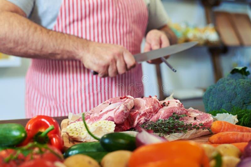 El tiro de la cosecha de manos afila el cuchillo antes de preparar la carne fotografía de archivo
