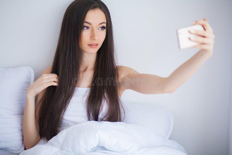 El tiro de la mujer linda feliz miente en cama usando el teléfono móvil fotografía de archivo