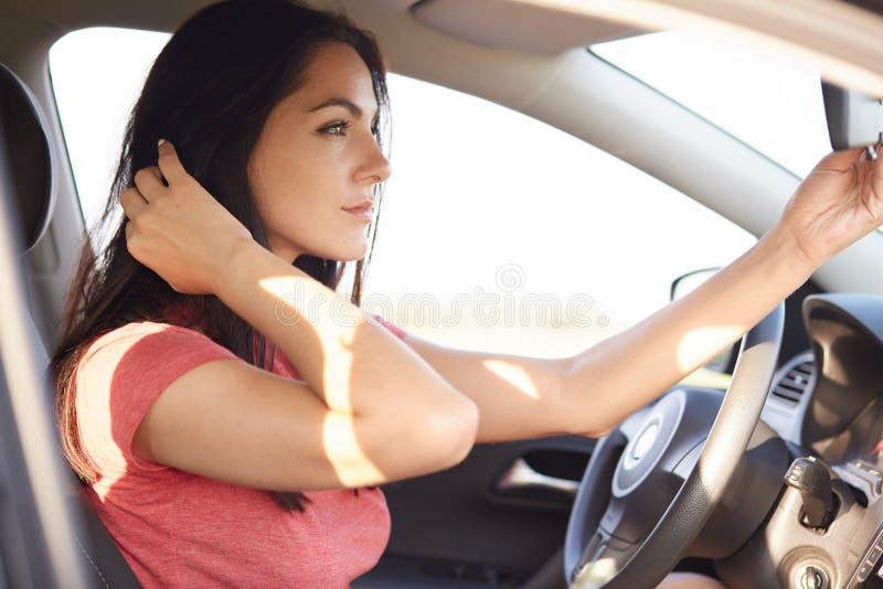 El tiro de la mujer morena hermosa se vistió en la camiseta casual, miradas seriamente en el espejo del coche, tiene expresión pe imagen de archivo libre de regalías