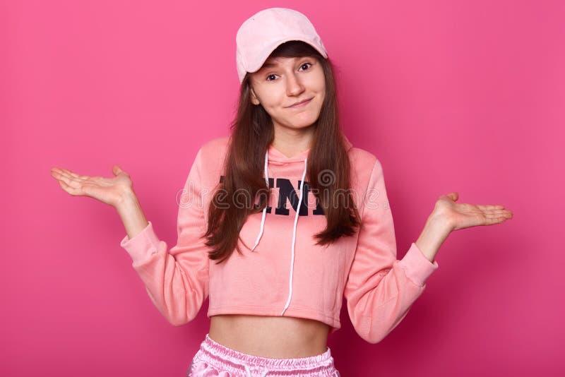 el tiro del adolescente bonito moreno atractivo, lleva sudadera con capucha color de rosa y el casquillo, mirando la cámara, tien fotos de archivo