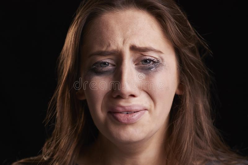 El tiro del estudio de la mujer joven gritadora con el ojo manchado compone fotos de archivo