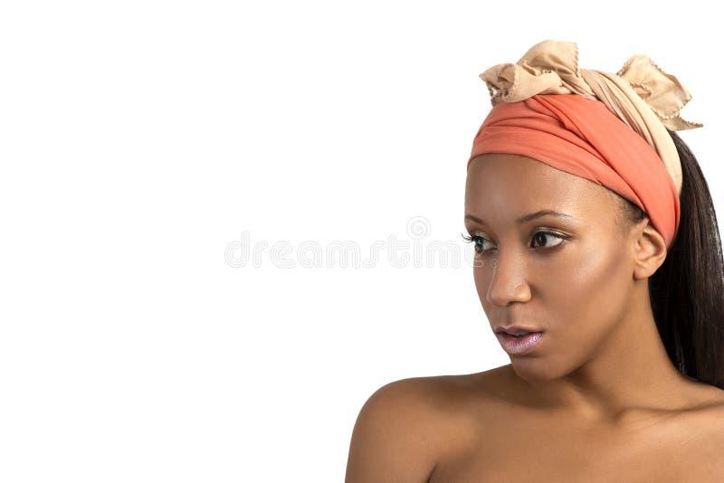 El tiro del estudio de la mujer joven del mulatta con compone el vendaje de la terracota en la cabeza en el dackground blanco foto de archivo