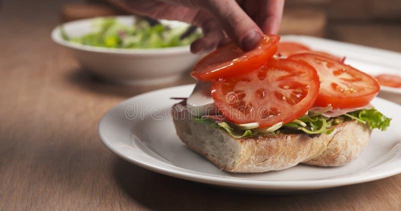 El tiro del tomate puso el pan del ciabatta que preparaba el bocadillo imagenes de archivo