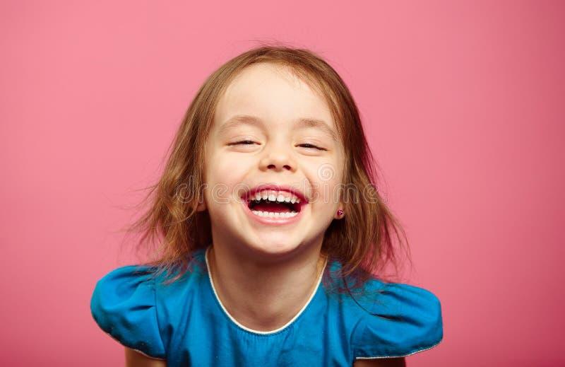 El tiro frontal de la niña alegre de la risa se coloca al lado de la pared rosada foto de archivo libre de regalías
