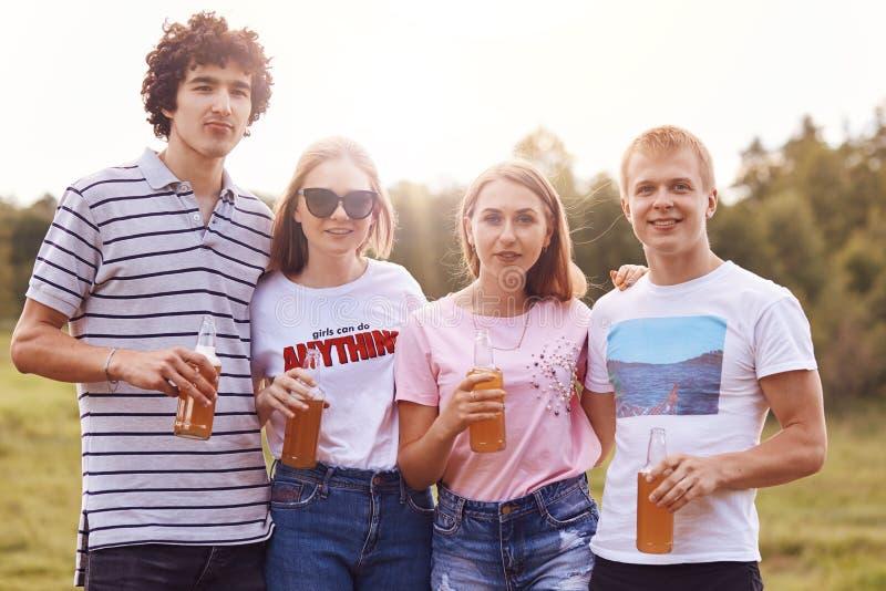 El tiro horizontal de cuatro adolescentes felices amistosos se coloca cerca de uno a, lleva las camisetas casuales, botellas del  fotos de archivo