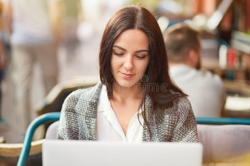 El tiro horizontal de la mujer cabelluda oscura seria envuelta en la sobrecama, trabajos sobre el dispositivo digital, informació imagen de archivo