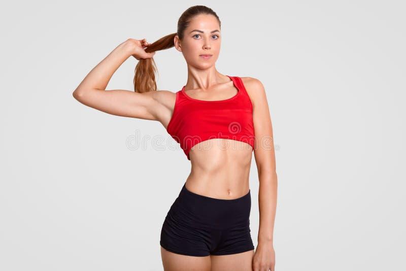 El tiro horizontal de la mujer deportiva delgada tiene cuerpo muscular sano agradable, vestido en top casual y pantalones cortos, fotografía de archivo
