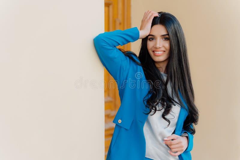 El tiro horizontal de la mujer joven morena sonriente mantiene una mano en la cabeza, vestida desgaste formal, tiene sonrisa dent foto de archivo