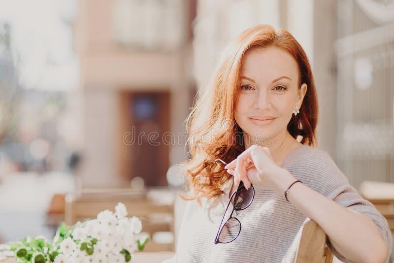 El tiro horizontal de la mujer pelirroja contenta atractiva se sienta en banco, disfruta de día soleado, sostiene las gafas de so foto de archivo
