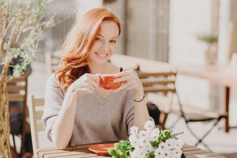 El tiro horizontal de la mujer pelirroja feliz sostiene la taza de bebida, con la expresión contenta, tiene flores en la tabla, d imagen de archivo