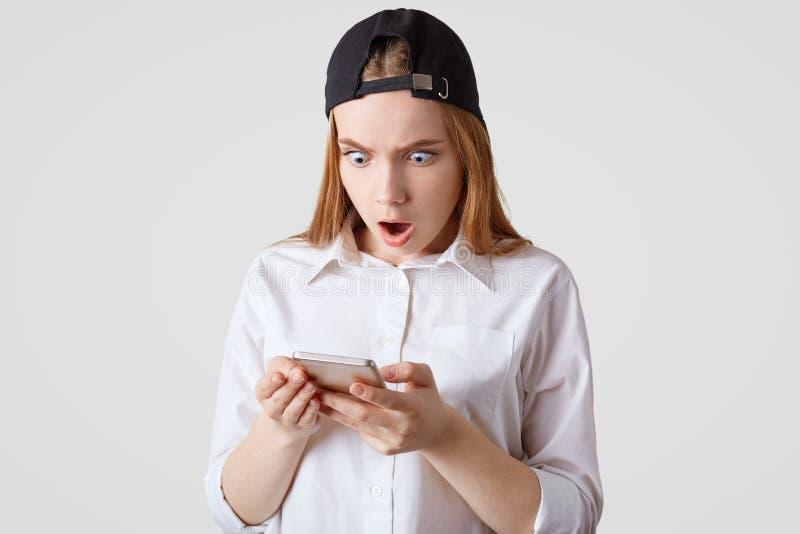 El tiro horizontal del adolescente en el casquillo y la camisa stilish, teléfono elegante de los controles, recibe el mensaje ine foto de archivo