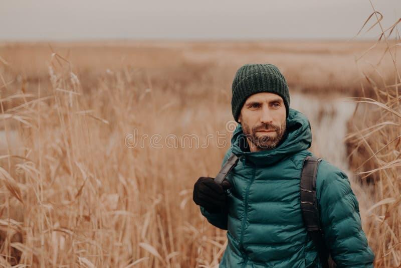 El tiro horizontal del hombre apuesto contemplativo tiene rastrojo, lleva el sombrero, la chaqueta y los guantes, soportes cerca  imágenes de archivo libres de regalías