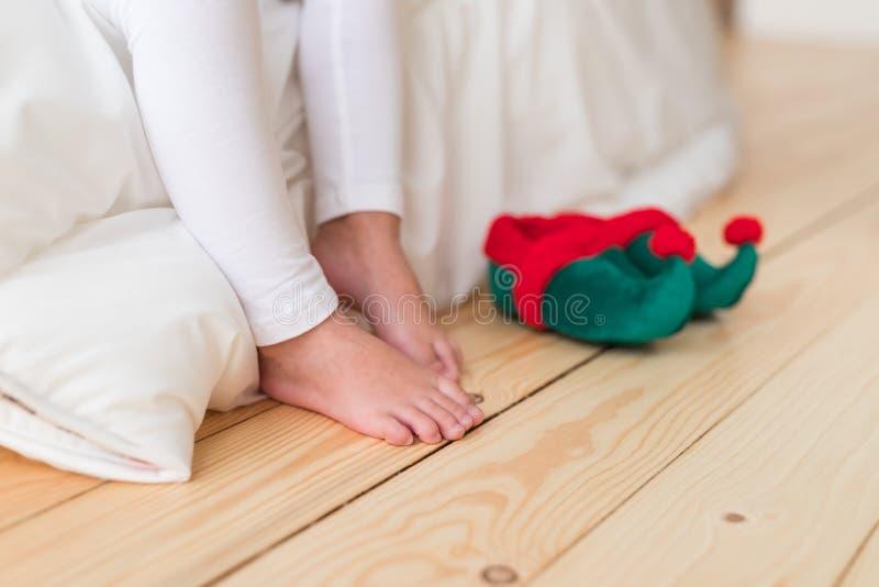 El tiro horizontal del pequeño pequeño niño irreconocible se coloca en piso de madera con el duende que s calza, se sienta en las foto de archivo libre de regalías